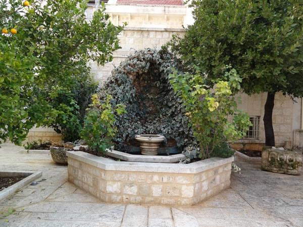 Nel cortile, una piccola grotta artificiale senza la classica presenza della statua della Vergine Maria.