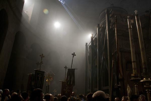 Un rai de lumière traverse la basilique où toutes les lampes sont éteintes tandis que se poursuit la procession autour de l'édicule