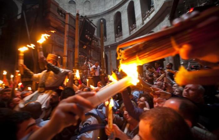 La flamme allumée par le Feu Sacré se répand parmi les fidèles dans l'Anastasis, le cur de la basilique. ©M.-A. Beaulieu/CTS