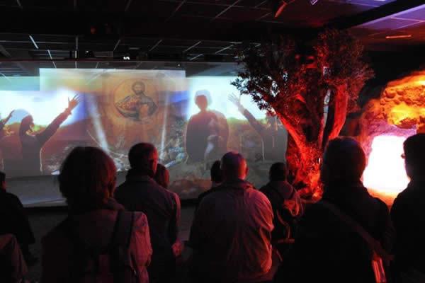 Un groupe de visiteurs observe le spectacle multimédia sur le rôle de Marie dans le mystère de l'Incarnation.