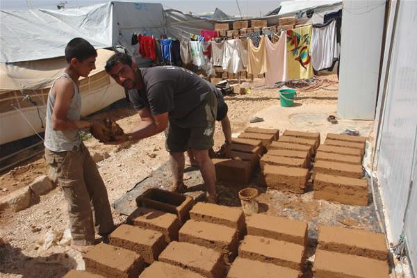 Des réfugiés du camp de Zaatari travaillant à la fabrication de briques artisanales pour construire une maison. (© C. Giorgi) [1/3]