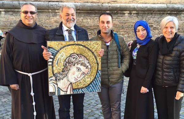 De gauche à droite, frère Ricardo Bustos et certains membres du Centre de mosaïque de Jéricho, avec la reproduction du visage du septième ange offert au pape François.
