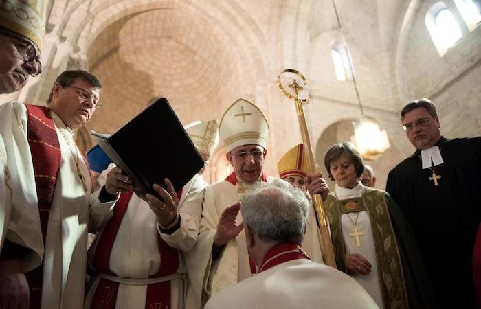 Le nouvel évêque, à genoux, sur le point d'être consacré.