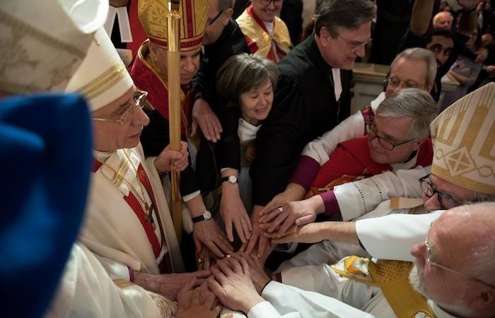 Les évêques concélébrants imposent les mains tous ensemble sur le pasteur Azar.