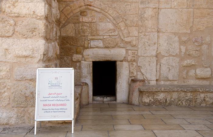 Devant la porte de l'humilité par laquelle on accède à la basilique de la Nativité, un panneau indique que le port du masque est obligatoire pour entrer. ©Nadim Asfour/CTS