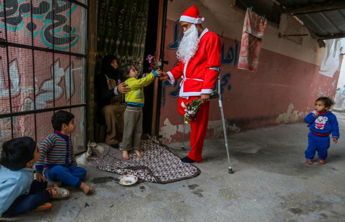 Un Palestinien déguisé en Père Noël distribue des fleurs dans le camps de réfugiés de Khan Yunis au sud de la bande de Gaza, le 24 décembre 2020. Abed Rahim Khatib/Flash90