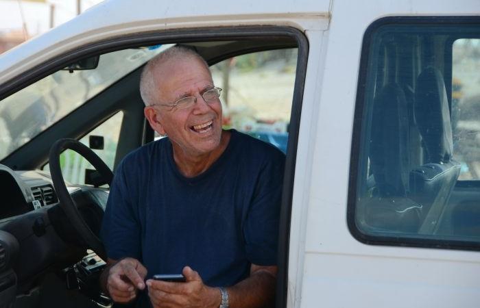 Yuval Roth souriant depuis le siège du conducteur de sa voiture. (Galerie de photos The Road to Recovery)