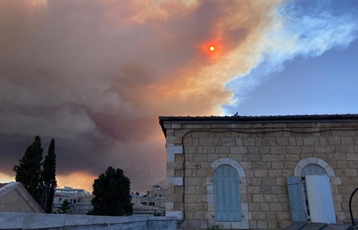 Masqué par un épais nuage ocre, le soleil rougeoie au dessus de Jérusalem ©Beatrice Guarrera