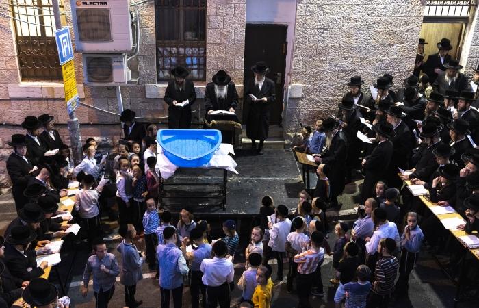 Des juifs ultra-orthodoxes accomplissent le rituel du Tashlich près d'une piscine en plastique contenant des poissons à Mea Shearim, le 14 septembre 2021 ©Olivier Fitoussi/Flash90